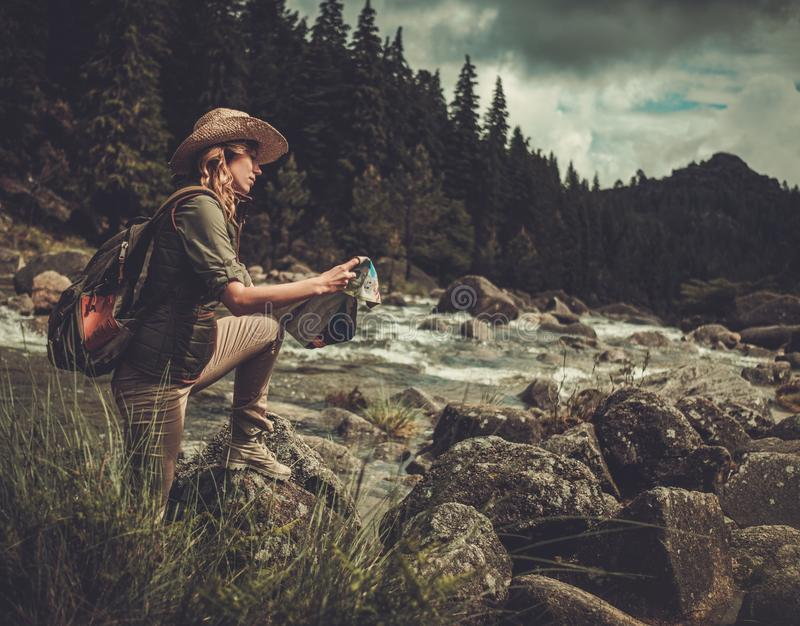Randonneur de femme, recherchant la bonne direction sur la carte près de la rivière de montagne images libres de droits