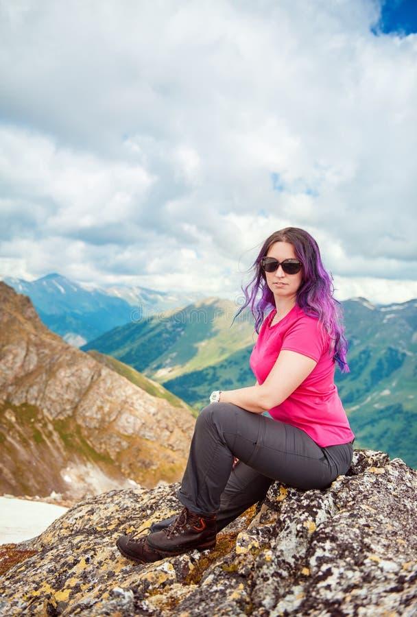 Randonneur de femme s'asseyant sur le dessus de la montagne photos stock