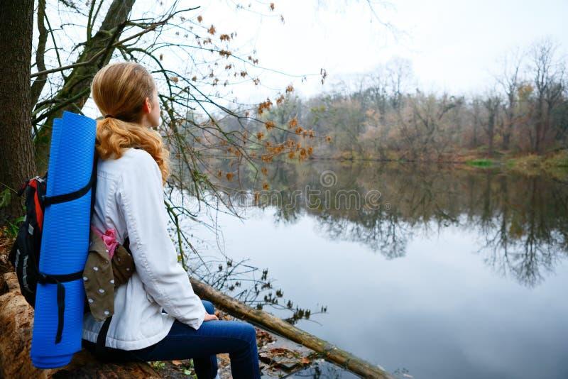 Randonneur de femme se reposant sur la rive photo stock