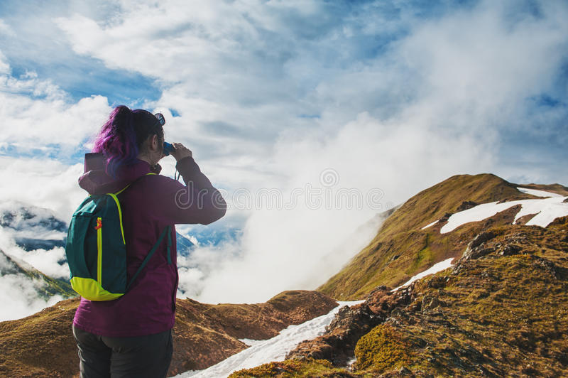 Randonneur de femme se tenant sur le dessus de la montagne et regardant dans le binoc images stock