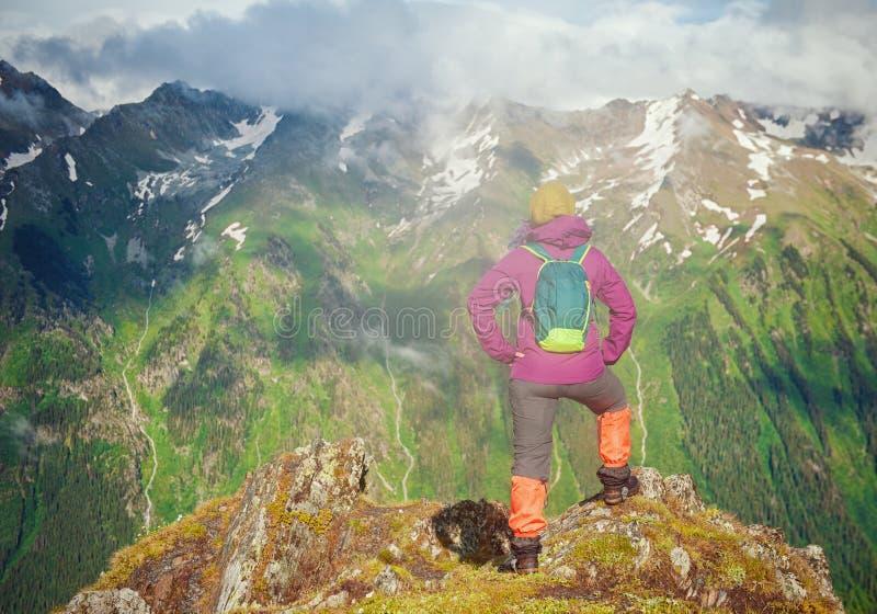 Randonneur de femme se tenant sur le dessus de la montagne Pose arrière image libre de droits