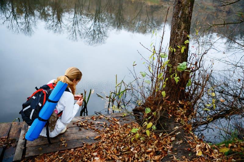 Randonneur de femme sur une plate-forme en bois en rivière d'automne images libres de droits