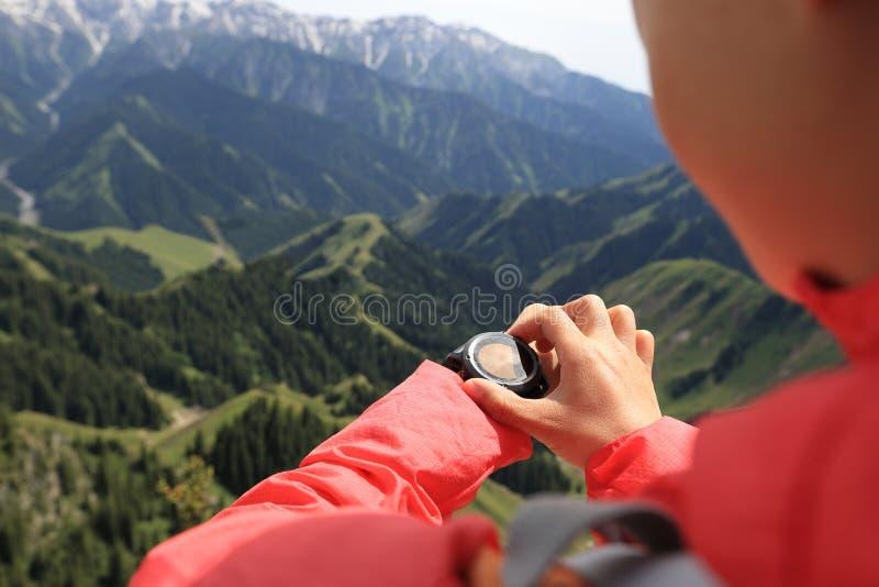 Randonneur de femme vérifiant l'altimètre sur la montre de sports à la crête de montagne images stock