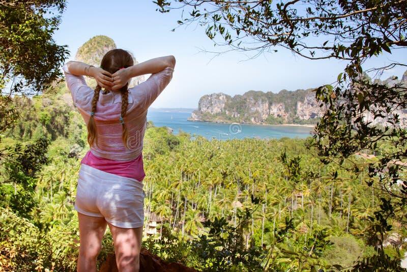 Randonneur de jeune dame avec des tresses de cheveux appréciant la vue de la plage tropicale à partir du dessus d'une montagne Me images libres de droits