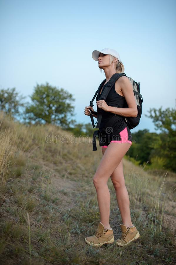 Randonneur de jeune femme avec le sac à dos se tenant sur la falaise et regardant le fa photographie stock
