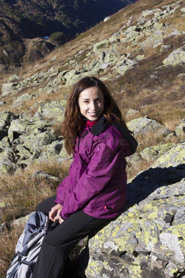 Randonneur de jeune femme faisant une coupure sur une roche image libre de droits