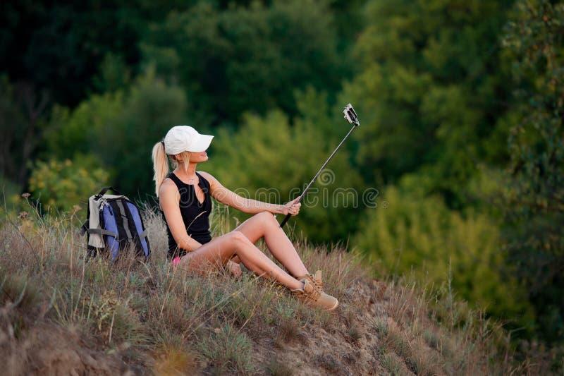 Randonneur de jeune fille, s'asseyant sur la colline avec le sac à dos image stock