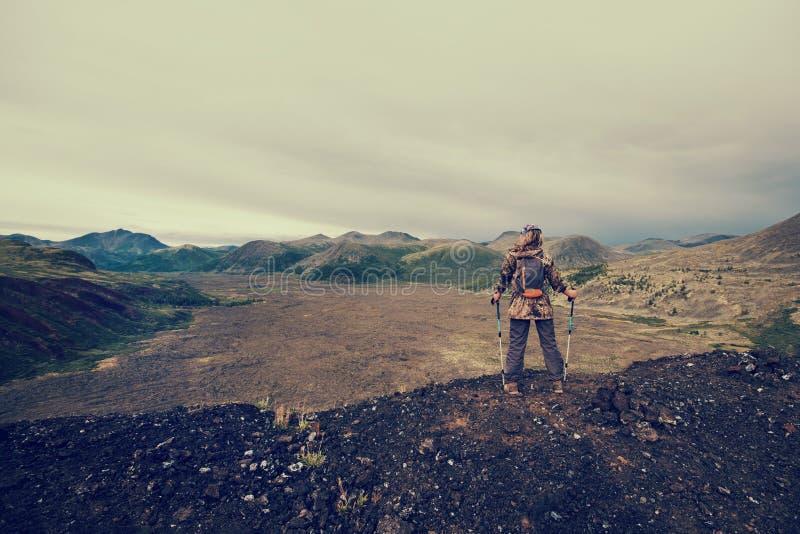 Randonneur de Madame avec le sac à dos se tenant sur la montagne, vue de crête de volcan à la vallée congelée de lave image stock