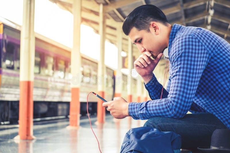 Randonneur de touristes à l'aide du téléphone portable pour voyager à la station de train image libre de droits