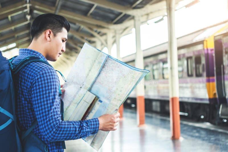 Randonneur de touristes employant la carte pour voyager ? la station de train image libre de droits