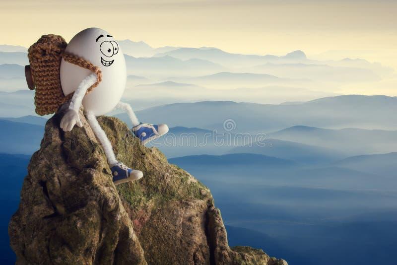 Randonneur drôle heureux d'oeufs s'asseyant sur une falaise image stock