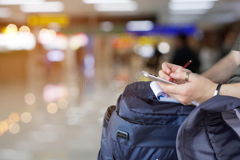 Randonneur examinant la carte sur le plan futé de téléphone pour assurer le voyage photographie stock