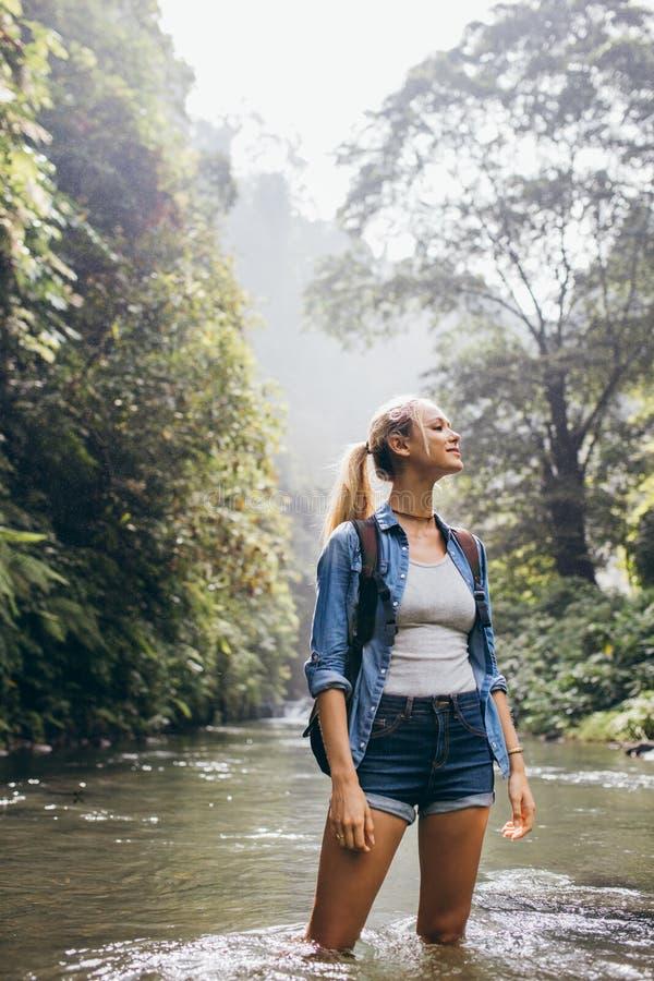 Randonneur féminin croisant la crique de forêt photographie stock