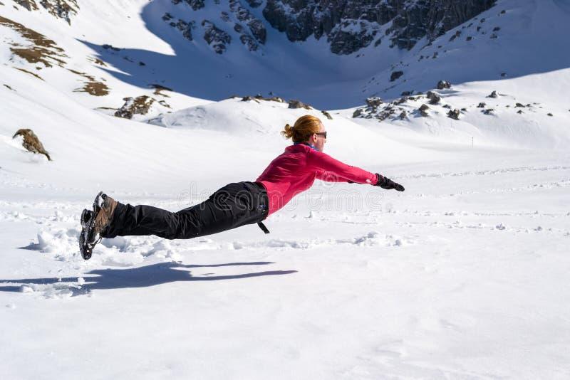 Randonneur féminin joyeux sautant sur la neige, horizontalement, ressemblant à une pose faisante de la lévitation de Superman/ image stock