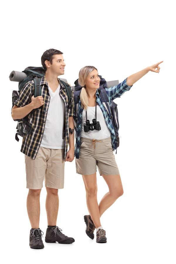 Randonneur féminin montrant quelque chose dans la distance à un randonneur masculin photographie stock