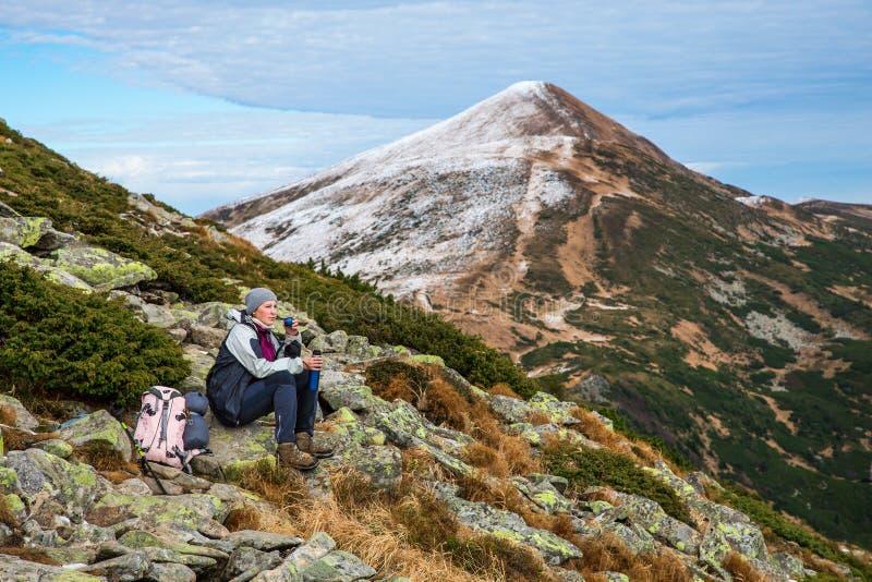 Randonneur féminin s'asseyant sur la pierre verte donnant sur le Mountain View scénique image stock