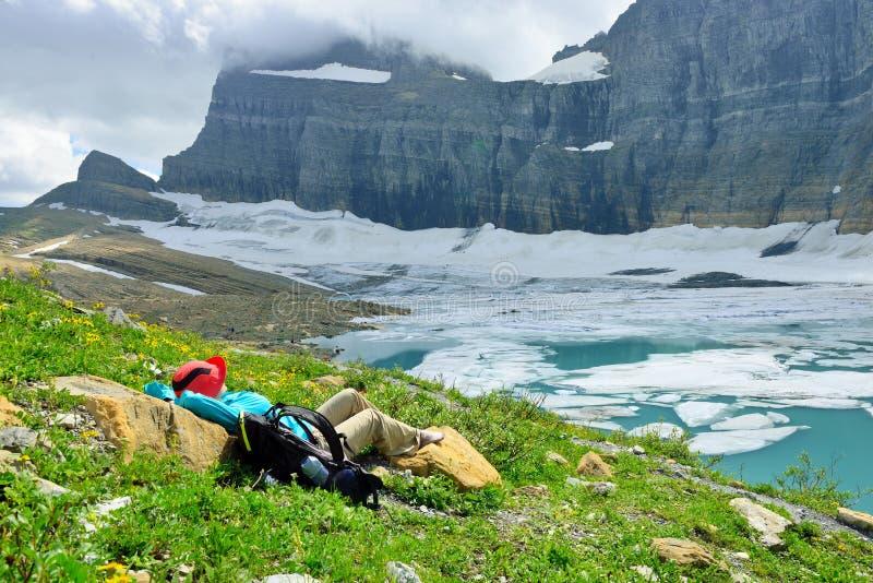 Randonneur féminin se reposant par le glacier de Grinnell en beaucoup de glaciers, G photographie stock