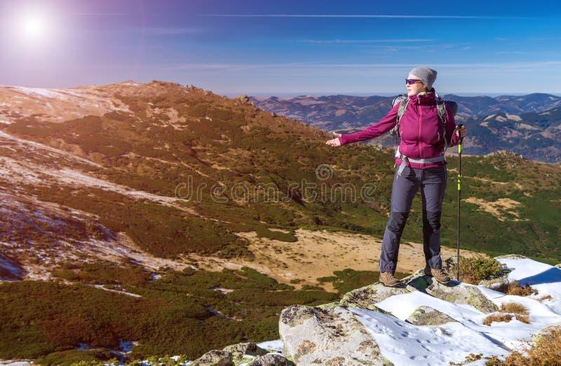 Randonneur féminin se tenant l'hiver scénique admiratif Mountain View Sun de roches neigeuses photo stock