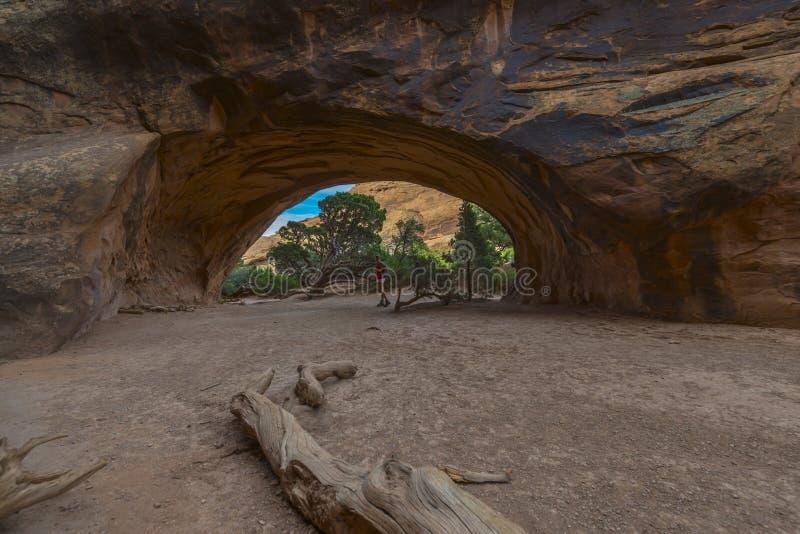 Randonneur féminin stading dans la voûte de Navajo au beau jour d'été près images stock