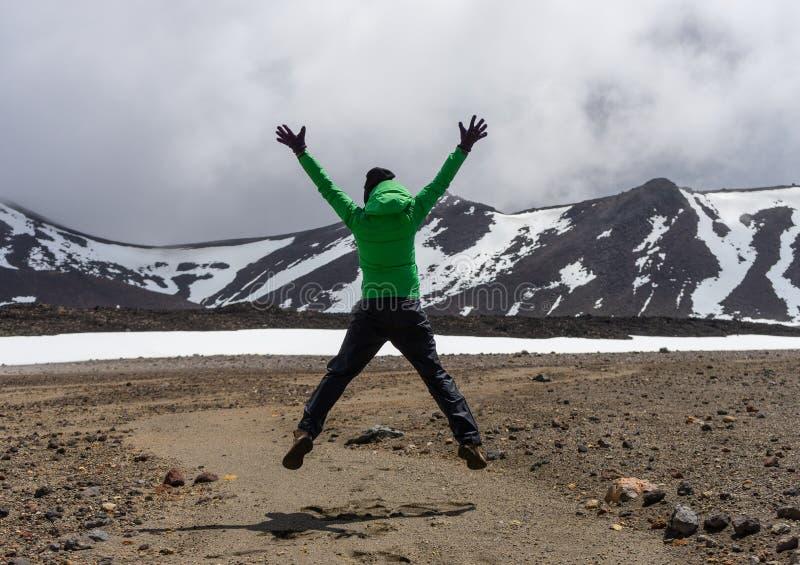 Randonneur heureux de femme sautant en parc national de Tongariro image stock