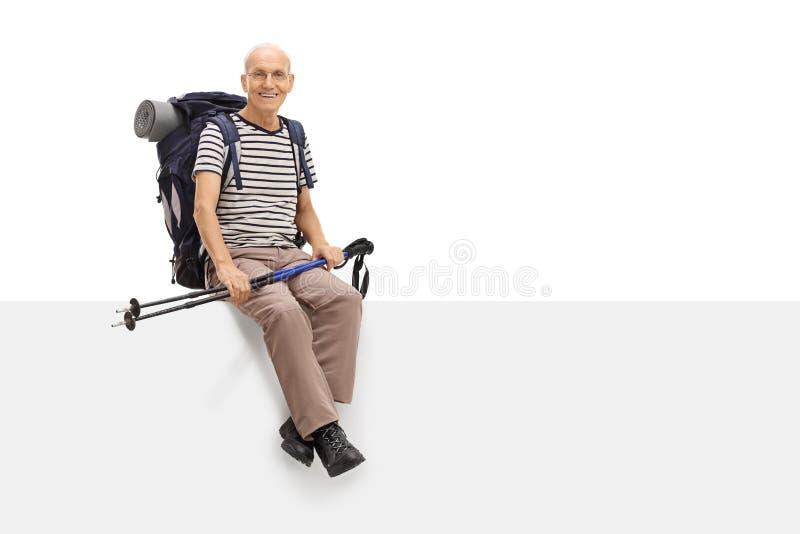 Randonneur mûr joyeux s'asseyant sur un panneau vide photo stock