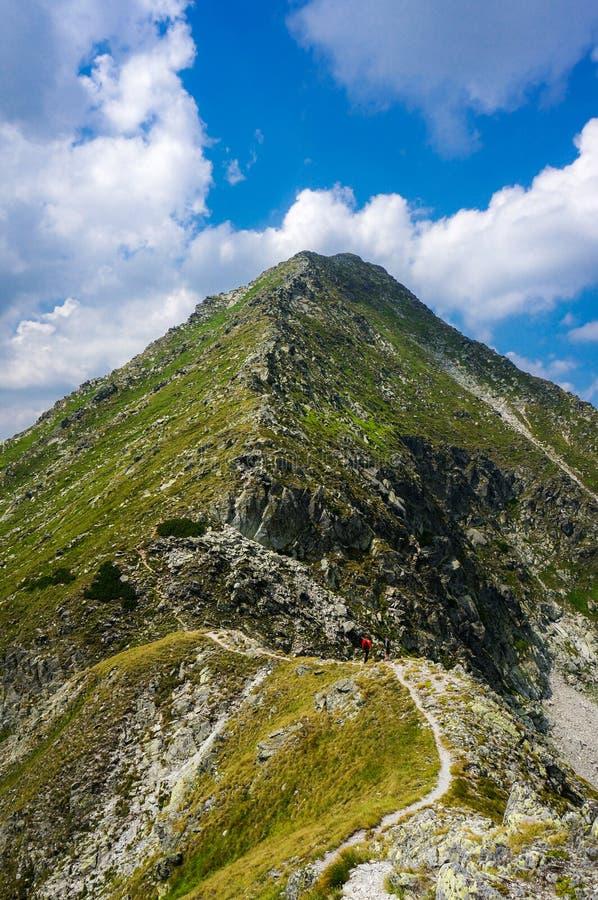 Randonneur marchant sur un chemin de touristes sur une arête pointue dans les montagnes photographie stock libre de droits