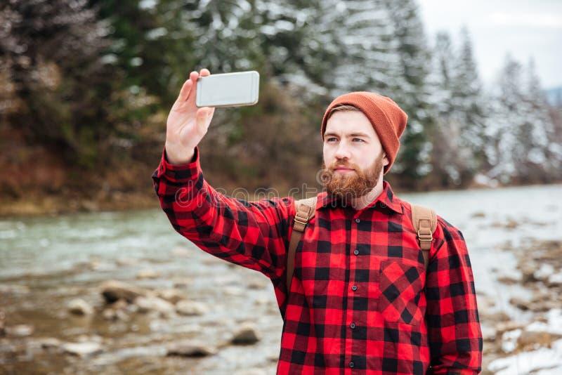 Randonneur masculin faisant la photo sur le smartphone photographie stock