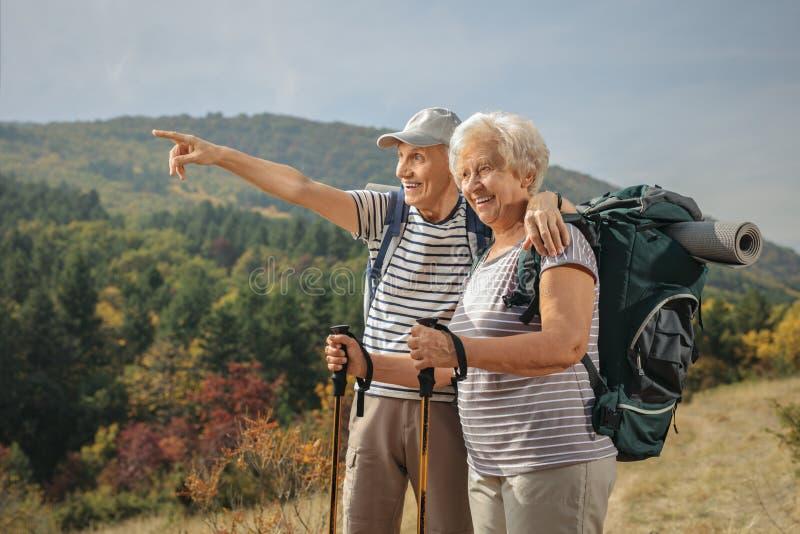 Randonneur masculin plus âgé montrant quelque chose dans la distance à un aîné images stock