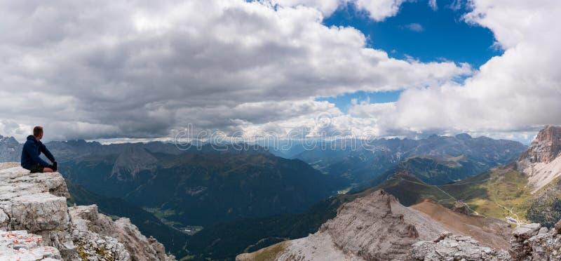 Randonneur masculin s'asseyant sur un rebord de crête de montagne dans les dolomites et regardant la vue étonnante photographie stock libre de droits