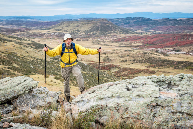 Randonneur masculin supérieur sur la falaise rocheuse photo libre de droits