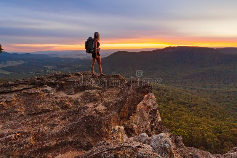 Randonneur observant la dernière lumière dans les montagnes images stock