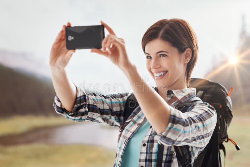 Randonneur prenant des photos avec un smartphone photographie stock libre de droits