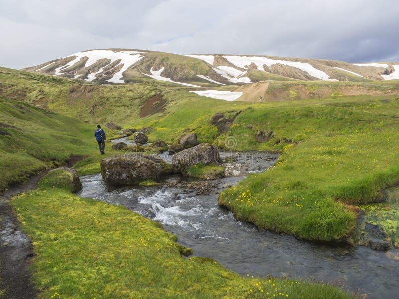 Randonneur seul d'homme marchant dans le paysage avec le courant sauvage de crique, g photo libre de droits