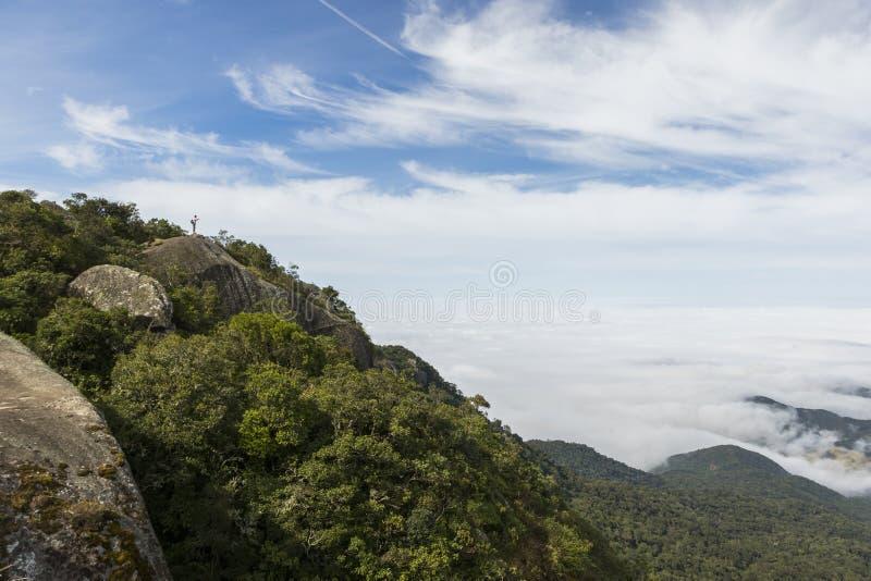 Randonneur solitaire au sommet de montagne au-dessus des nuages photographie stock libre de droits