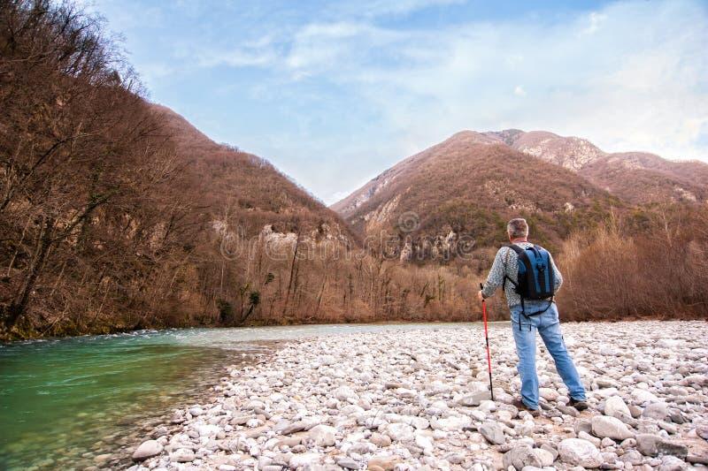 Randonneur supérieur sur la banque d'une rivière Marche vers la montagne Retraite active photos stock