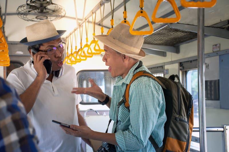 Randonneurs asiatiques fâchés ayant un problème et discutant le voyage par chemin de fer photos libres de droits