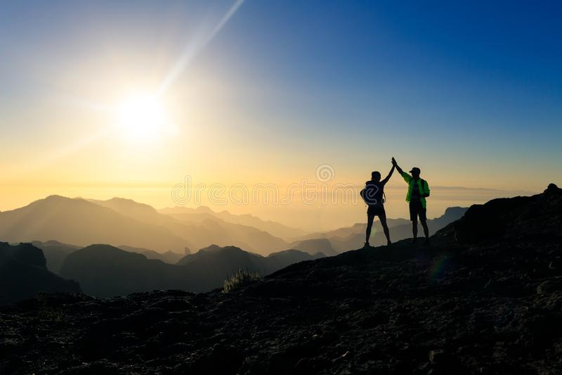 Randonneurs de couples célébrant le concept de succès en montagnes photos stock