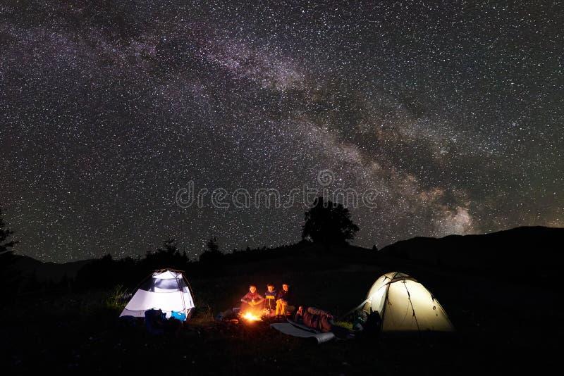 Randonneurs de famille ayant un repos au camping de nuit en montagnes images stock