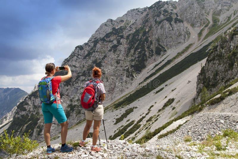 Randonneurs marchant sur la hausse dans le paysage de nature de montagne et prenant des photos photographie stock libre de droits