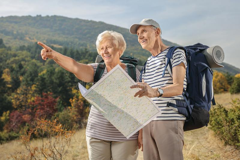 Randonneurs pluss âgé tenant une carte et un pointage génériques photographie stock