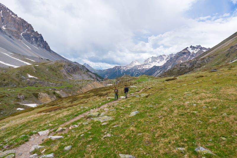 Randonneurs s'élevant vers le haut sur la traînée de montagne rocheuse raide Aventures et exploration d'été sur les Alpes Ciel dr image libre de droits