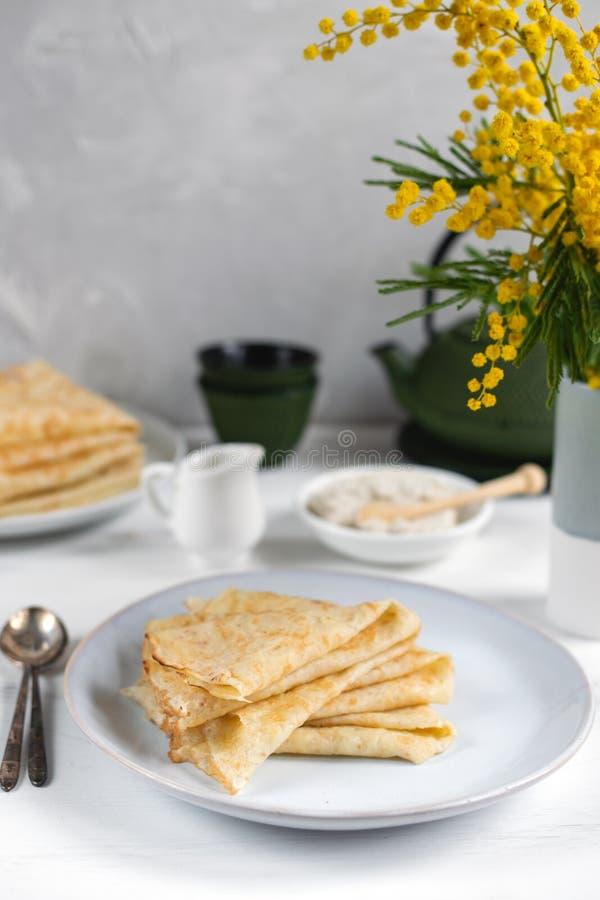 Ranek, śniadanie - tradycyjni rosyjscy blini bliny, francuskie krepy batożąca śmietanka, obsady żelaza zieleni teapot, mimoz obrazy stock