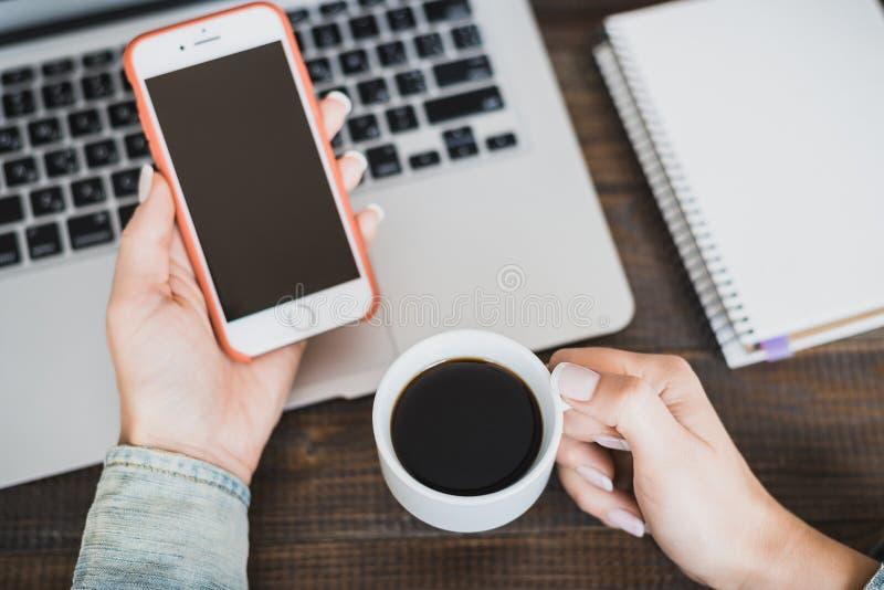 Ranek biznesowa kobieta Laptop na biurku, telefonie i filiżance kawy w żeńskich rękach, Horyzontalna rama zdjęcia stock