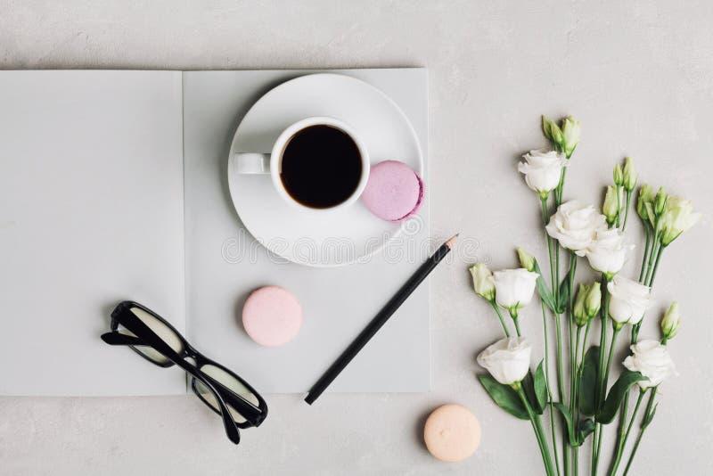 Ranek filiżanka kawy, pusty notatnik, ołówek, szkła, biali kwiaty i tortowy macaron na lekkim stołowym odgórnym widoku, obraz royalty free