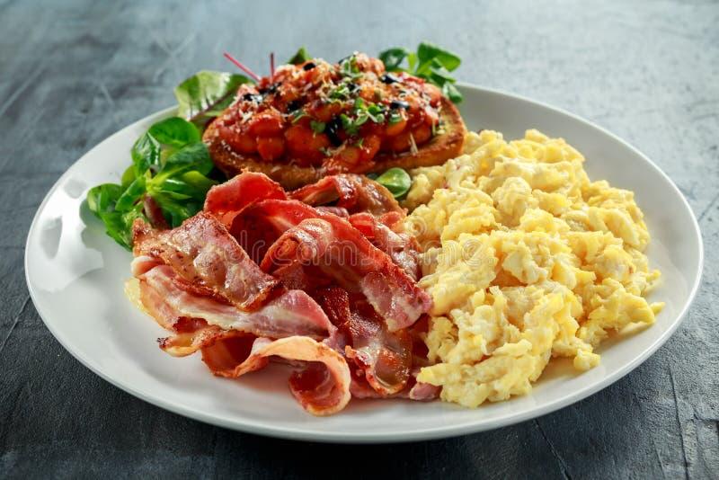 Ranek Gramolił się jajko, bekonowy śniadanie z fasolami w pomidorowym kumberlandzie na wznoszącym toast chlebie na bielu talerzu obrazy stock