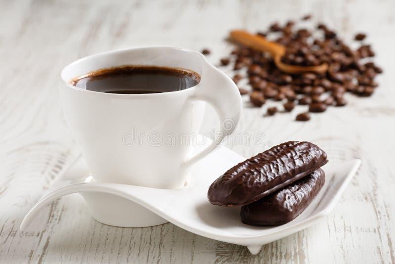 Ranek kawa w białej ceramicznej filiżance z fala kształtował spodeczek i dwa kakaowego ciastka na białym drewnianym wieśniaka sto obraz stock