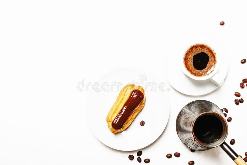 Ranek kawa z eclair tortem, biały tło, odgórny widok obrazy stock