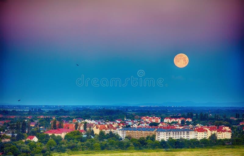 ranek księżyc nad miastem w dolinie Uzhhorod, Ukraina zdjęcia stock