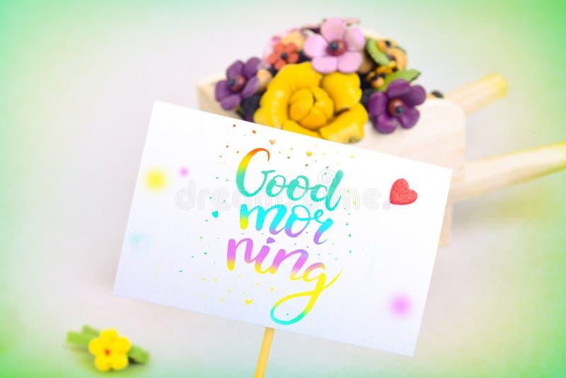 Ranek niespodzianka, wheelbarrow z kwiatami i karta, Barwiona inskrypcja jest dniem dobrym obraz royalty free
