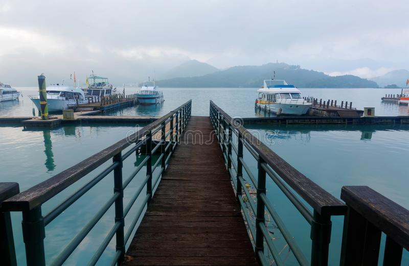 Ranek sceneria zwiedzające łodzie cumować spławowi doki drewniany molo brzeg jeziora mgłowe góry & zdjęcie royalty free